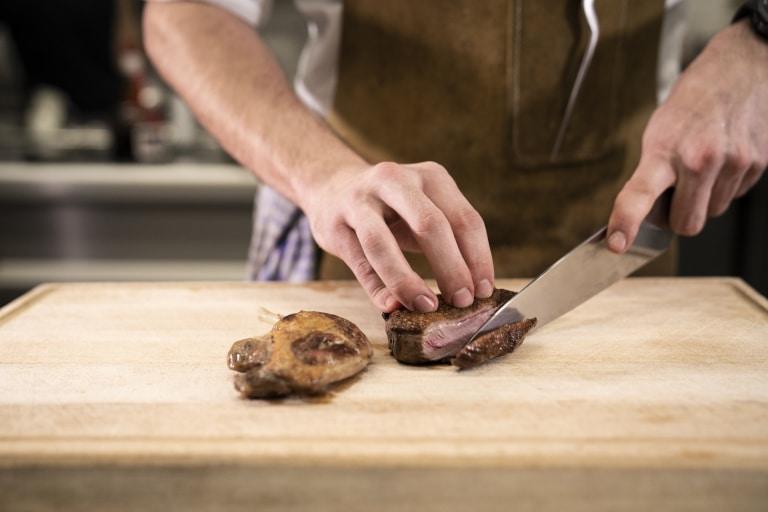 Koch schneidet ein Stück Fleisch auf