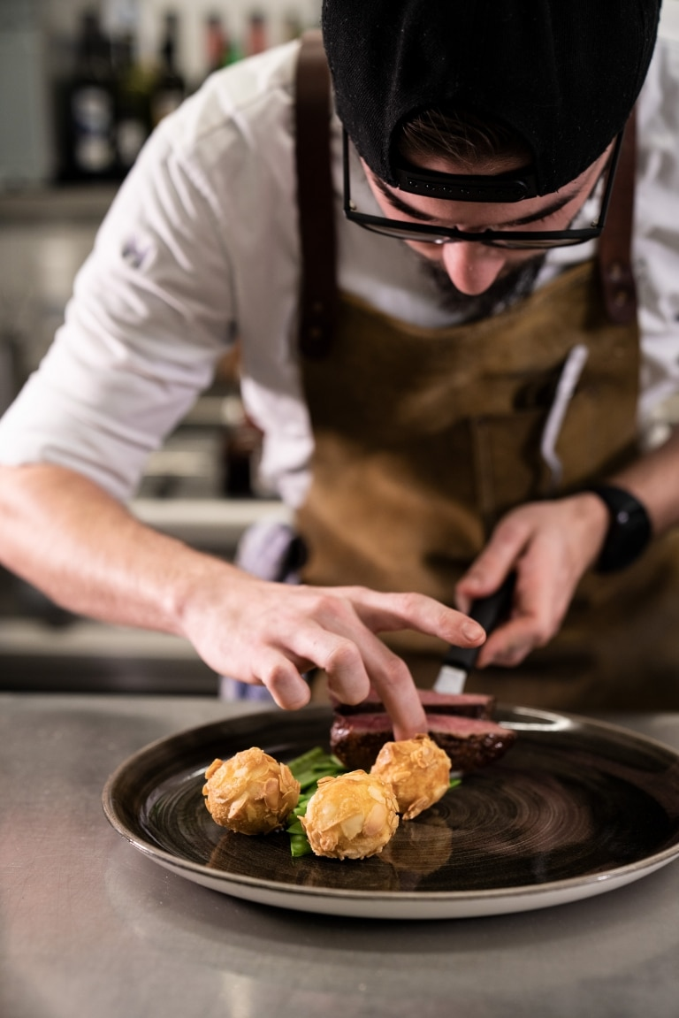 Blick auf Koch der Essen auf Teller zubereitet