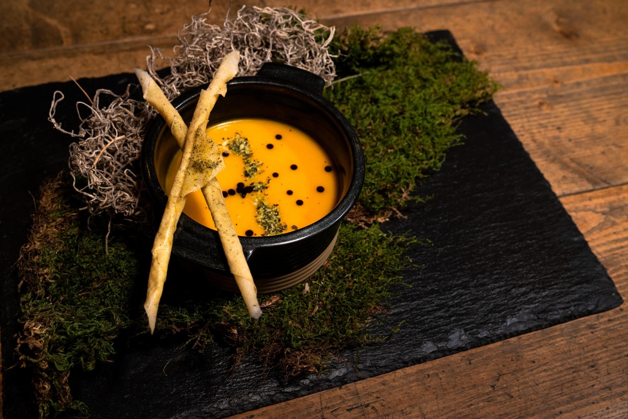 Schwarze Platte mit Deko, darauf Schüssel mit Suppe