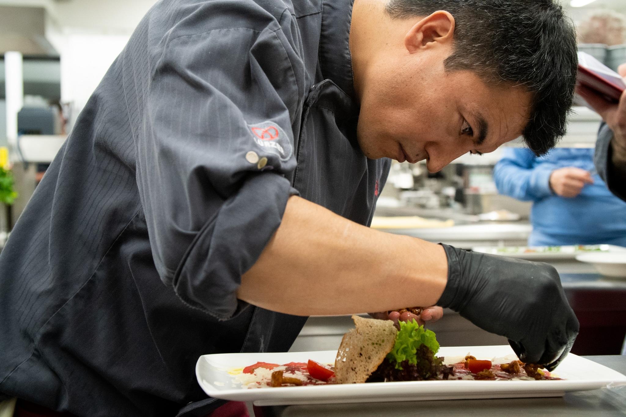 Koch mit Handschuhen bereitet Mahlzeit zu